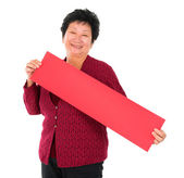 Chinese senior woman with red spring couplets — Stock Photo