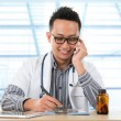 Stock Photo: Asian medical doctor working on desk