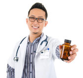 Asian medical doctor holding a bottle of pills — Stock Photo