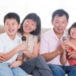 Asian family singing karaoke — Stock Photo