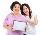 Asian family holding a blank board — Stock Photo