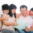 Parents and children reading books at home. — Stock Photo