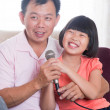 Happy Asian family singing karaoke — Stock Photo