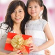 Royalty-Free Stock Photo: Asian girl giving a gift to her happy mother