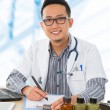 Asian medical doctor working on his desk — Stock Photo #22315219