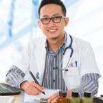 Aziatische medische arts werkzaam op zijn Bureau — Stockfoto