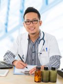 Asian medical doctor working on his desk — Stock Photo