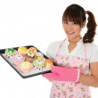 Young Asian girl baking bread and cupcakes — Stock Photo
