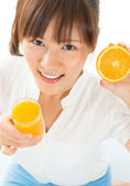Asian girl drinking orange juice — Stock Photo