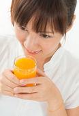 Asian female drinking orange — Stock Photo