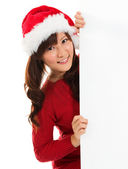 Christmas girl peeking from behind blank sign billboard. — Stok fotoğraf