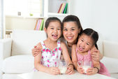 Mother and daughters drinking milk — Stock Photo