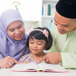 Malay Muslim family reading a book. — Stock Photo
