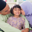 Foto Stock: Muslim parents kissing child.