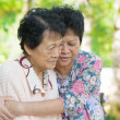 Asimature womhugs and consoling her crying old mother — Stock Photo #29558343