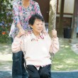 Asian senior women playing swing at outdoor garden park — ストック写真