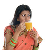 Indian woman drinking orange juice — Stock Photo