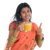 Thumb up Indian woman drinking orange juice — Stock Photo