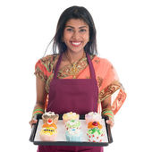 Traditional Indian woman baking bread and cupcakes — Stock Photo