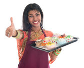 Thumb up Indian woman baking cupcakes — Stock Photo