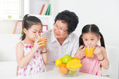 Asian children drinking orange juice — Stock Photo