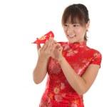 Chinese cheongsam girl peeking into red packets — Stock Photo