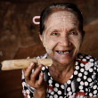 Happy old wrinkled Asian woman smoking — Stock Photo #30967335