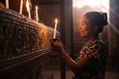 Asian woman praying with candle light — Stock Photo