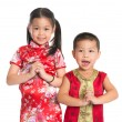 Stock Photo: Little oriental children wishing you a happy Chinese New Year