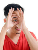 Asian man peeping through fingers hole — Stock Photo