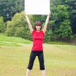 Outdoor Asian girl with placard — Stock Photo