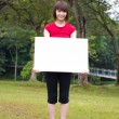 Stock Photo: Asian girl holding a placard outdoor