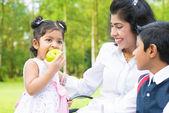 Indian girl eating apple — Stock Photo