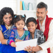 Indian family using tablet pc computer at home — Stock Photo