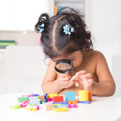 Indian girl zoom into toys through a magnifying glass — Stock fotografie