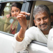 Indian man showing his new car key. — Stockfoto #47663571