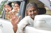 Indian family waving hands in car — Stock Photo