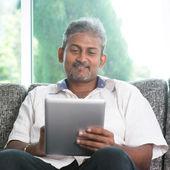 Indian man using digital tablet computer — Stock Photo