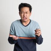 Man holding medicine bottle while sneezing — Stock Photo