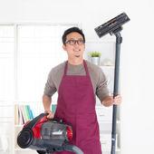 Asian man vacuuming — Stock Photo