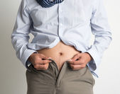 Man trying to fasten pants — Stock Photo