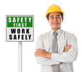 Asian male wearing yellow hardhat with safety first sign board. — Stock Photo