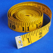 A coiled-like measuring tape isolated on blue background — 图库照片