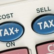 Calculate the tax and the cost with a calculator - Stock Photo