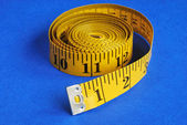 A coiled-like measuring tape isolated on blue background — Stock Photo