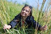 žena v sluneční brýle vypadá v trávě s ušima — Stock fotografie