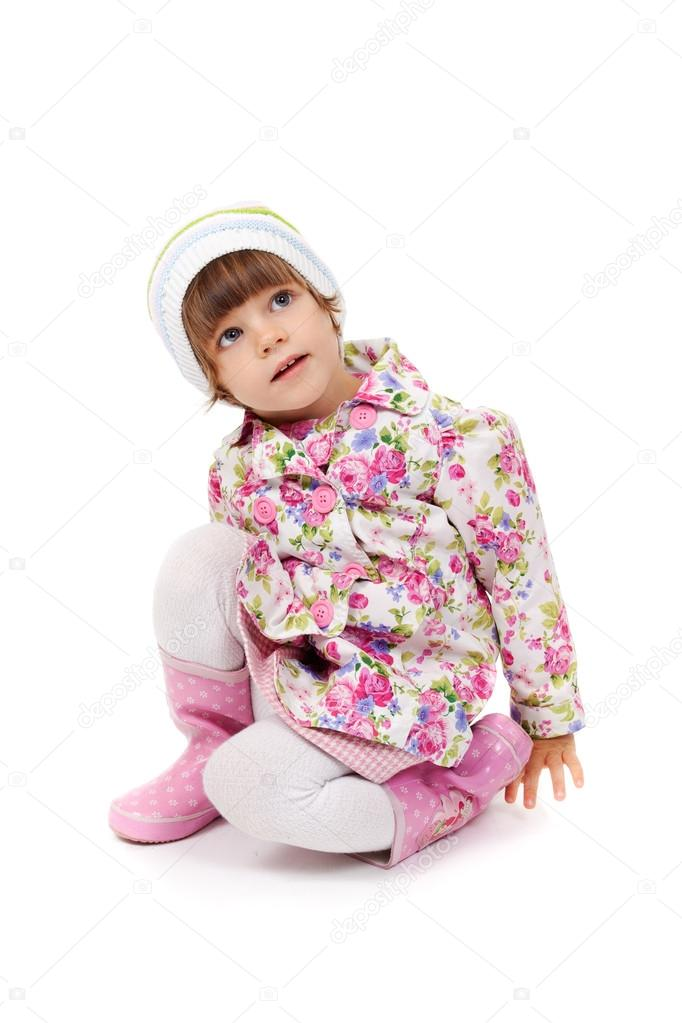 Little girl in boots and a jacket sitting on the studio floor  Stock Photo #12568158