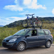 Two bicycles mounted on roof of car against sky — Stock Photo