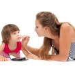 Young mother paints lipstick little daughter in the studio — Stock Photo