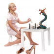 Beautiful blonde girl playing chess with a decorative dragon — Stock Photo #13437209